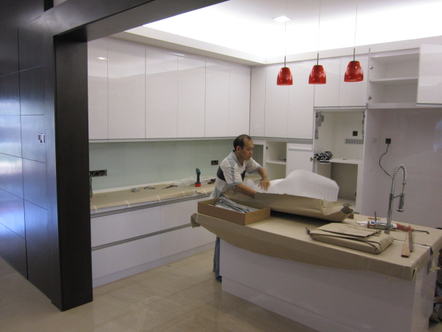 Our experienced workers in action white glossy kitchen cabinets with
